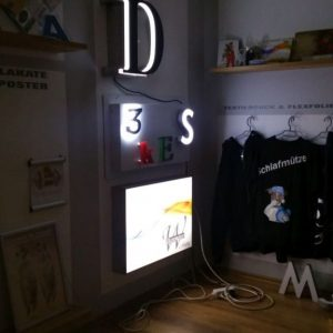 Leuchtmittelwerbung als Buchstaben und Leuchtkasten an der wand befestigt