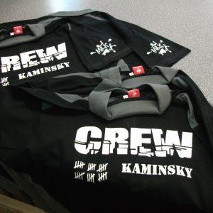 Crew Kaminsky Kragen Tshirt von Engelbert und Strauß in Schwarz Grau mit Crew Kaminsky Logo Hagenah, Strichliste und Milch Spritzer Schriftzug Milk