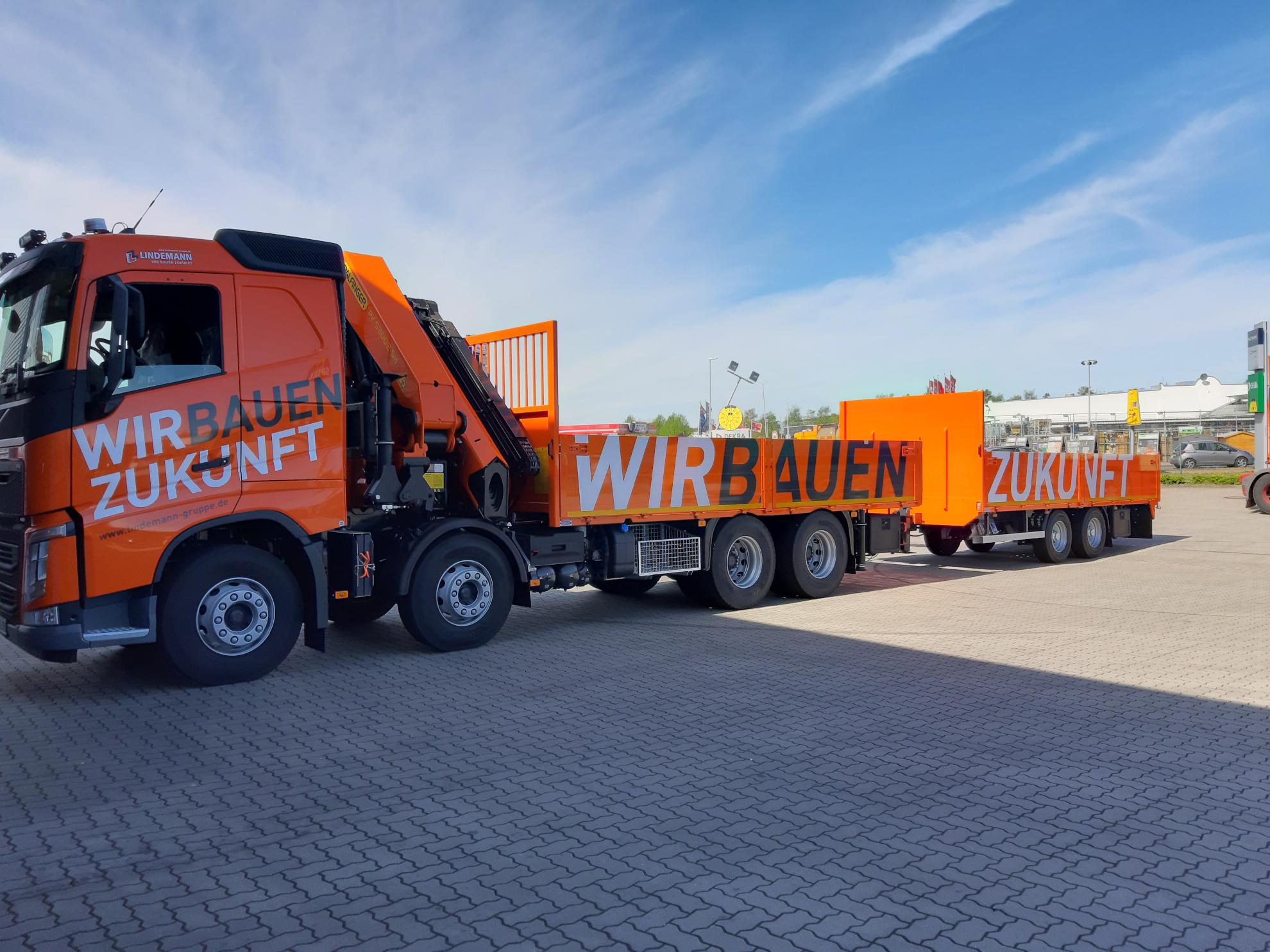 Lindemann LKW in Orange mit beschriftung wir bauen Zukunft